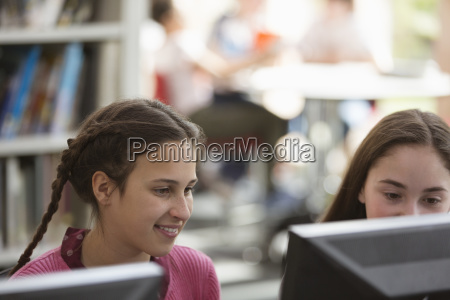 girl students researching using computer in