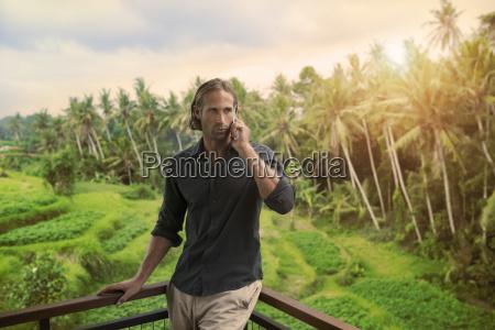 handsome man leaning on balkony speaking