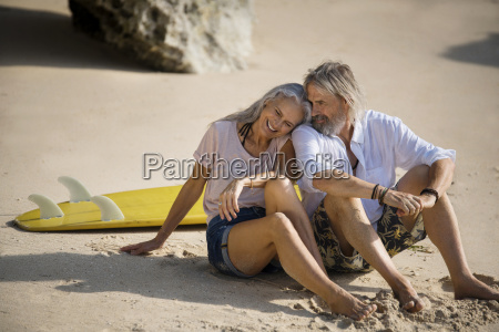 affectionate senior couple with surfboard lying