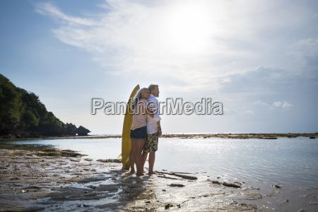 affectionate senior couple with surfboards at