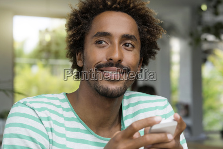 smiling man with smartphone in a