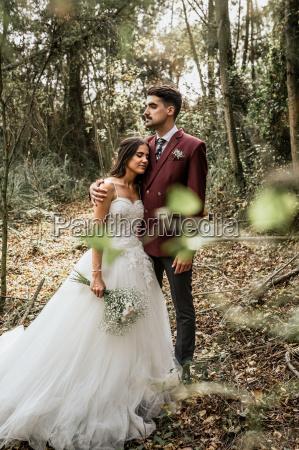 groom embracing bride with closed eyes