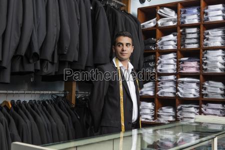 elegant tailor standing in tailor shop