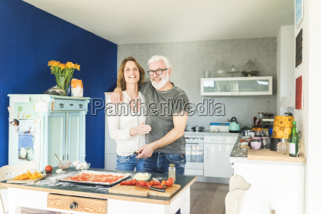 happy mature couple embracing in kitchen