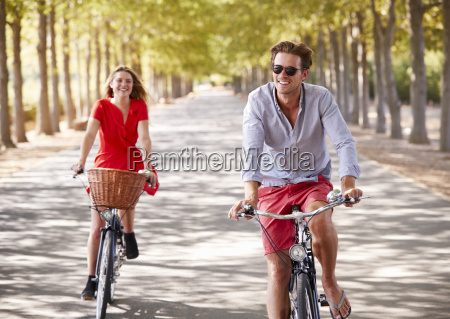 young white adult couple riding bikes