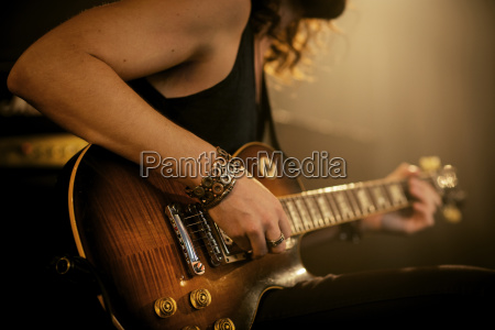midsection of man practicing guitar in