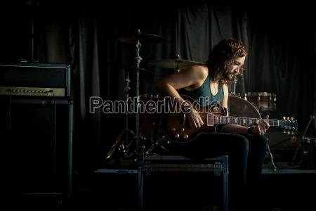 musician practicing guitar in rock music
