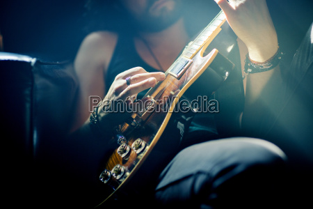 midsection of musician practicing guitar in