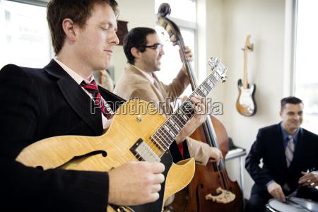 men playing musical instruments in studio