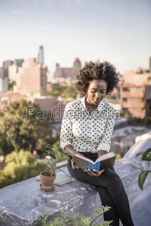 smiling woman reading book while sitting