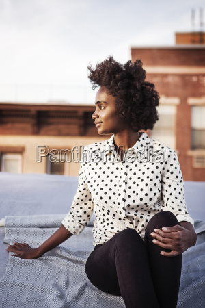 smiling woman sitting on building terrace