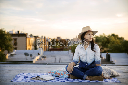 thoughtful woman sitting by book on