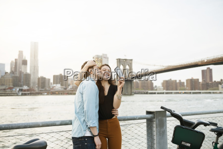 man kissing happy woman photographing against