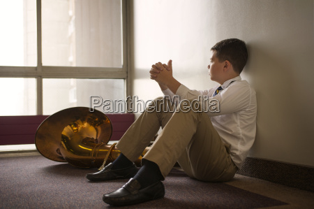thoughtful boy sitting by tuba on