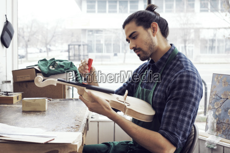 instrument maker working on violin in