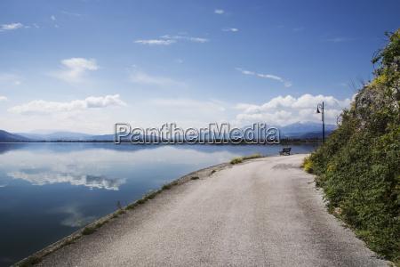 vanishing road by lake against blue
