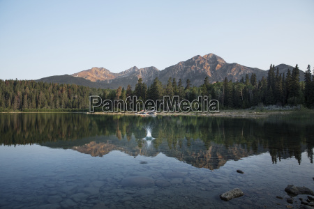 reflection of mountains and trees in