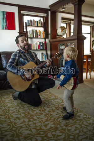 father with son singing while playing