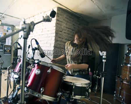 happy woman enjoying while playing drum