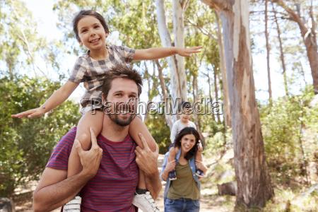 children riding on parents shoulders on