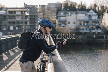 senior man with cyclist helmet using