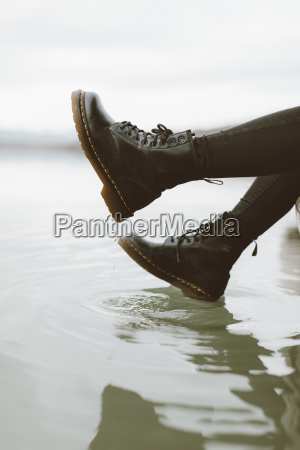 woman wearing black boots touching water