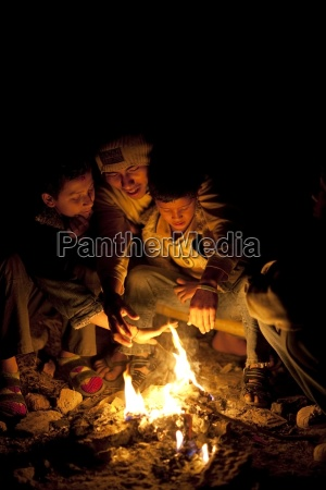 young men sitting around a fire