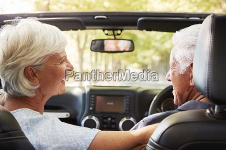 senior couple drive open top car