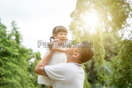 happy father and daughter bonding outdoors