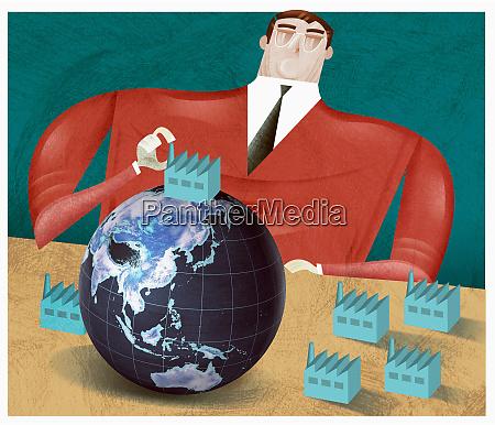 businessman putting factory on globe