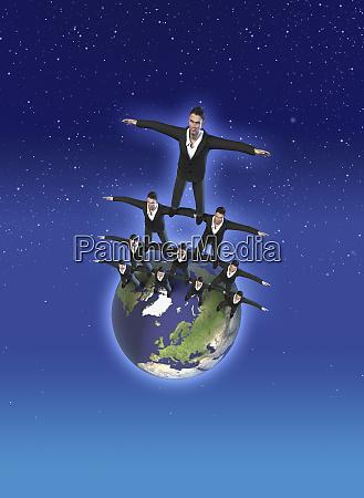 businessmen balancing on earth