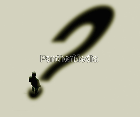 man casting large question mark shadow