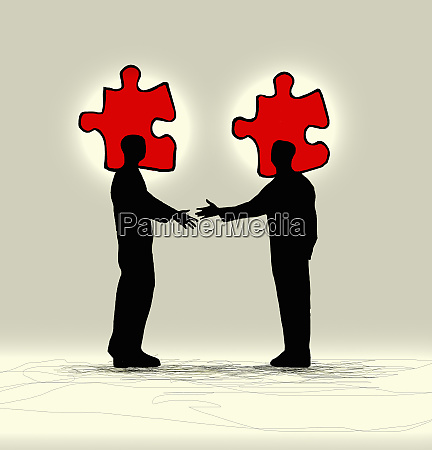 businessmen shaking hands with matching jigsaw