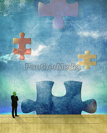 man contemplating large jigsaw puzzle pieces