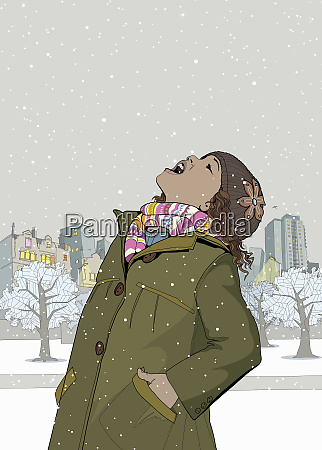 little girl catching snowflakes with mouth