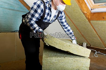 man installerer termisk tag isolering lag