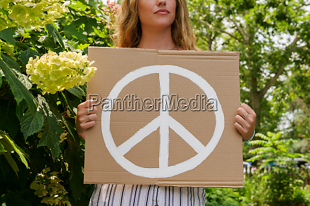 woman holding peace symbol by trees