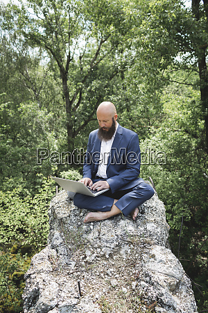 bald bearded businessman working over laptop