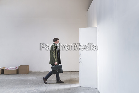 businessman with briefcase leaving sparse room