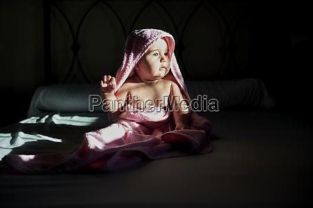 cute baby girl in towel looking
