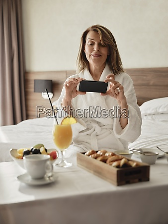smiling blond senior woman photographing breakfast