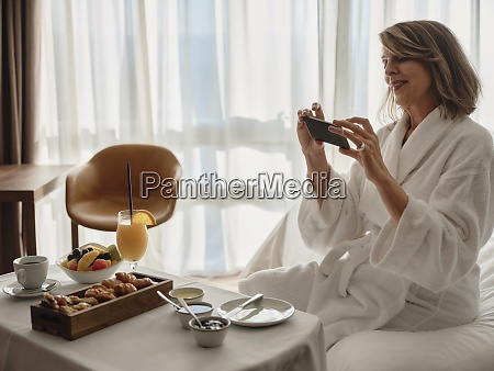 smiling blond elderly woman photographing breakfast