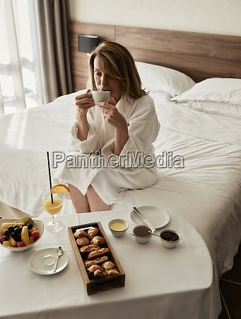blond senior woman drinking coffee while