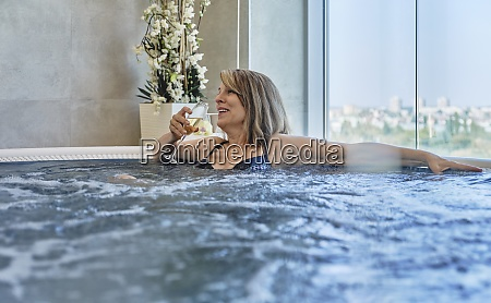 happy woman drinking in swimming pool