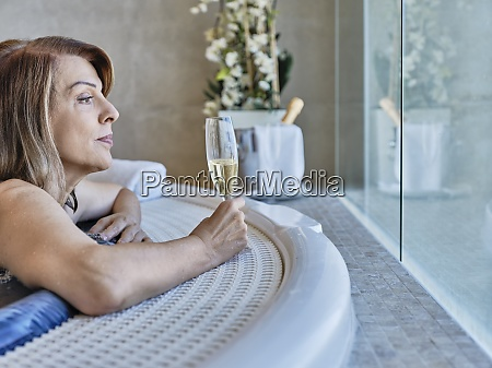 senior woman looking through window while